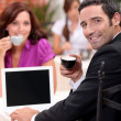 Stock Photo: Couple drinking expresso in a cafe with a laptop screen left blank for your