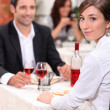 Couple at restaurant with woman turned to camera - Stock Photo