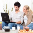 Couple using a laptop computer at breakfast — Stock Photo