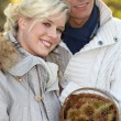 Couple dressed in warm clothes, woman is holding a wickerwork basket full — Stock Photo #7952855