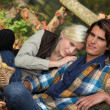 Couple sitting in dead leaves — Stock Photo #7952894