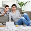 Couple sat on couch with laptop and newspaper — Stock Photo