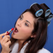 Woman in rollers applying lipstick — Stock Photo