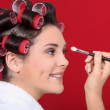 Woman with hair curlers applying make-up — Stock Photo