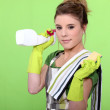 Housewife holding a sponge and a product — Stock Photo #7954030