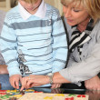 Grandmother helping her grandson with a puzzle — Stock Photo