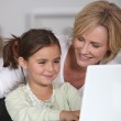 Mother and young daughter using a white laptop computer together — Stock Photo