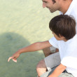 Father and son sat on jetty — Stock Photo #7954923