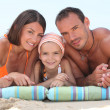 Family laying on beach — Stock Photo