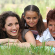 Grandmother, mother and daughter lying in the grass — Stock Photo #7955116