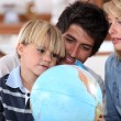 Young family looking at a globe — Stock Photo #7955358