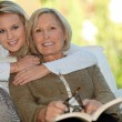Girl with her grandmother reading a book — Stockfoto