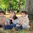 Three little girls playing with soap bubble solutions in the forest - Stock Photo