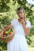 Summery woman with a basket of fruit — Stock Photo
