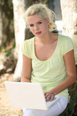 Blond girl in park with laptop — Stock Photo