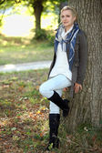 Woman leaning against tree — Stock Photo