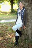 Vrouw leunend tegen boom — Stockfoto