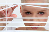 A blonde woman looks through blinds — Stock Photo