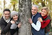 Adult family around a tree — Stock Photo