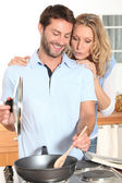 Young couple cooking in kitchen — Stock Photo