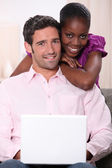 Mixed couple with laptop — Stock Photo