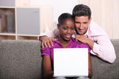 Couple sat at home looking at laptop computer — Stock Photo