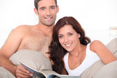 Couple reading a magazine in bed — Stock Photo