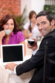 Couple drinking expresso in a cafe with a laptop screen left blank for your — Stock Photo