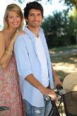 Couple on bike ride through park — Stock Photo