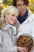 Couple dressed in warm clothes, woman is holding a wickerwork basket full — Stock Photo