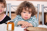 Grumpy toddler waiting to eat pancakes — Stock Photo