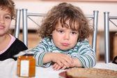 Grumpy toddler waiting to eat pancakes — Stock Photo