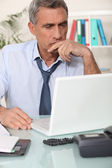 Grouchy man reading an email — Stock Photo