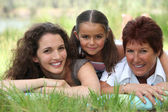 Grandmother, mother and daughter lying in the grass — Stock Photo