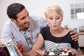 Woman blowing out a candle on her birthday — Stock Photo