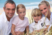 Young family in the sand dunes — Stock Photo