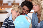 Young family looking at a globe — Stock Photo