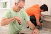 Father and son putting together flatpack furniture — Stock Photo