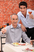 Father and son having meal together — Stock Photo
