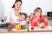 Kids cooking with their mother — Stock Photo