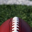 Football close up with yard line beyond — Stock Photo