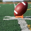 American Football teed up for kickoff - Stock Photo