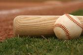 Baseball & Bat on the field — Stock Photo