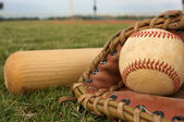Baseball in a glove with bat — Stockfoto