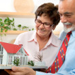 Senior couple holding a model of their dream house — Stock Photo