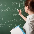 Girl writing on a chalkboard — Stock Photo