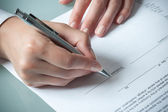 Female hands filling out employment agreement contract — Stock Photo