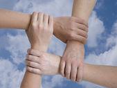 Spojené ruce na pozadí oblohy — Stock fotografie