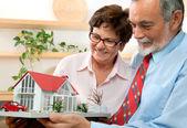 Couple de personnes âgées maintenant un modèle de leur maison de rêve — Photo
