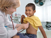 Femmina medico esaminando il ragazzino figlio — Foto Stock
